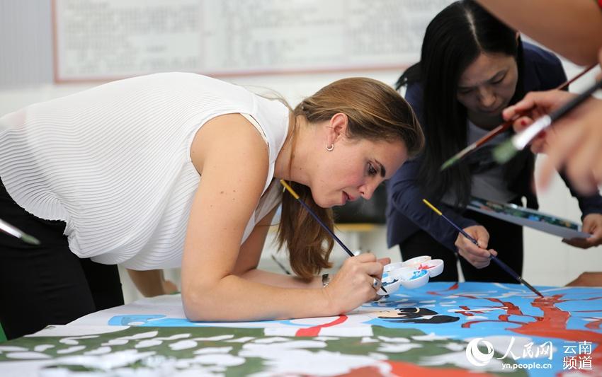 """冈特`鲍利夫人凯瑟琳娜与学校师生一起绘制""""彝族农民画""""。(人民网 虎遵会 摄)"""
